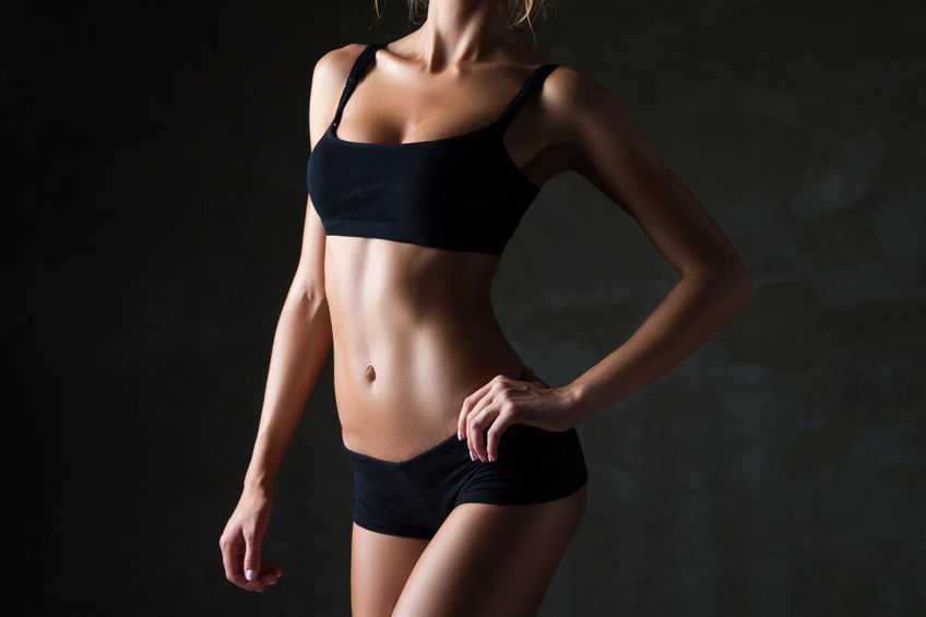 Slim tanned woman's body over dark gray background