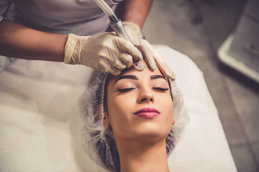 Beautiful young woman is getting face skin treatment. Doctor in medical gloves is undertaking the procedure using modern equipment